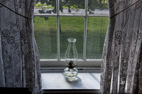 Oil Light in Window with Lace Curtains